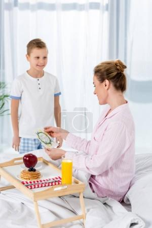 little son giving breakfast in bed for mother on mothers day