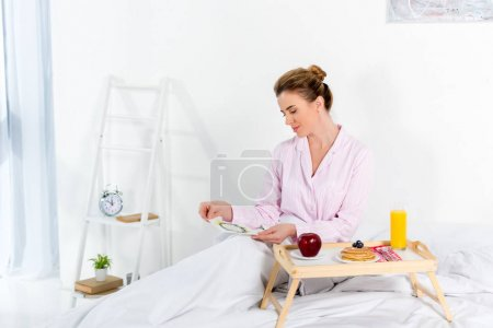 woman in pajamas with breakfast in bed and mothers day greeting card
