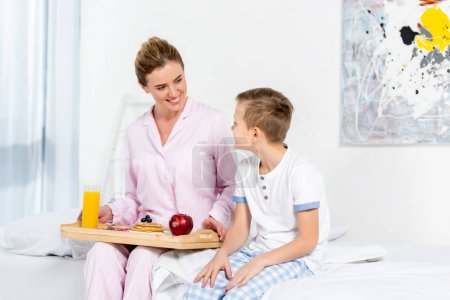 Photo for Mother holding breakfast on wooden tray made by her son - Royalty Free Image
