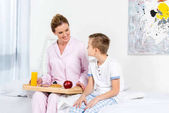 mother holding breakfast on wooden tray made by her son