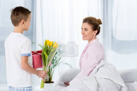 son holding gift and flowers for happy beautiful mother on mothers day morning