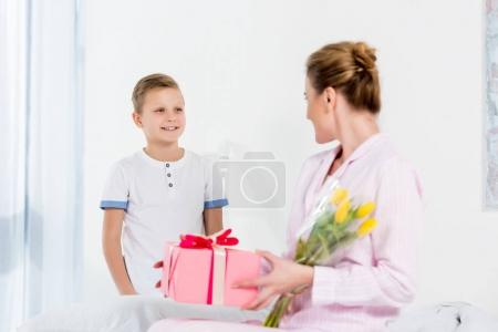 mother with gift and flower bouquet presented by little son on mothers day morning