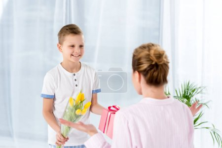 happy little son presenting gift and flowers for mother on mothers day morning