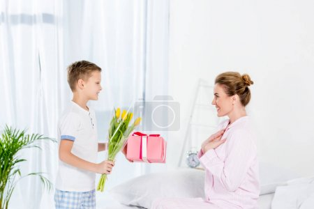 little son presenting gift and flowers for mother on mothers day morning