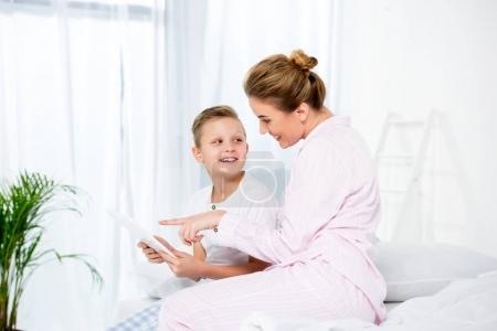 mother and son using tablet together in bed in morning