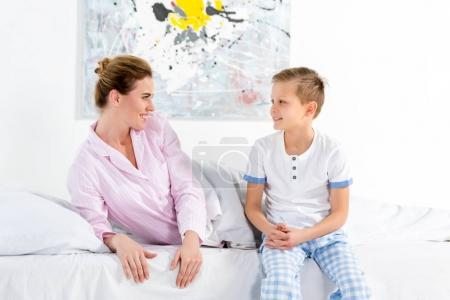 happy mother and son sitting in bed in morning