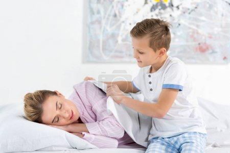 Photo pour Petit garçon portant sur sa mère endormie avec couverture - image libre de droit