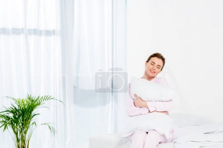 happy woman embracing pillow while sitting on bed in morning