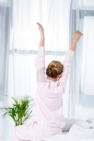 rear view of woman stretching after wake up