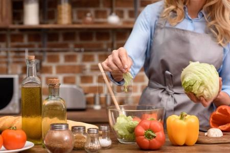 cropped image of woman adding salad leaves to salad