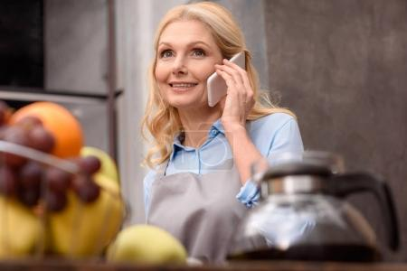 beautiful woman talking by smartphone in kitchen and looking away