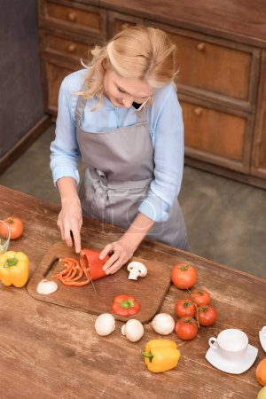 high angle view of woman talking by smartphone while cutting vegetables