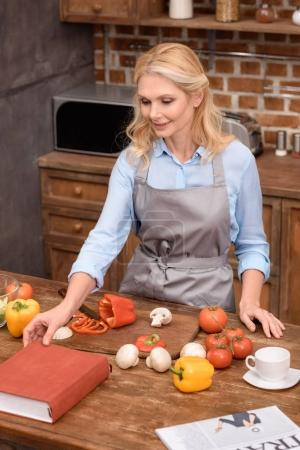 woman taking recipe book in kitchen