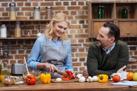 Photo for Smiling husband looking at wife while she cutting vegetables - Royalty Free Image