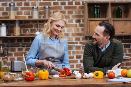 Lächelnder Ehemann schaut Frau beim Gemüseschneiden an