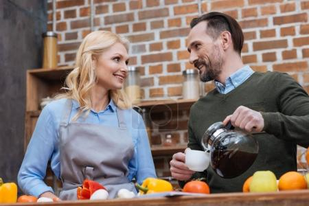 husband pouring coffee in cup for wife