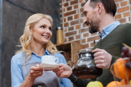 husband proposing coffee to wife in kitchen