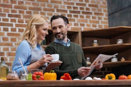 Photo for Husband showing something in newspaper to wife - Royalty Free Image