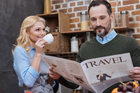 wife drinking coffee and husband reading travel newspaper