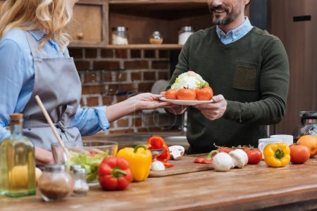 cropped image of wife giving plate with vegetables to husband
