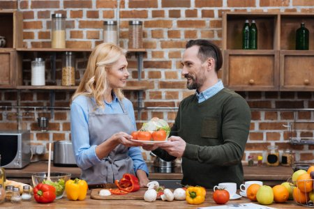 Photo for Husband giving plate with vegetables to wife - Royalty Free Image