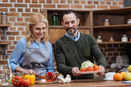 Photo pour Femme coupe légumes et mari mettre assiette sur la table - image libre de droit