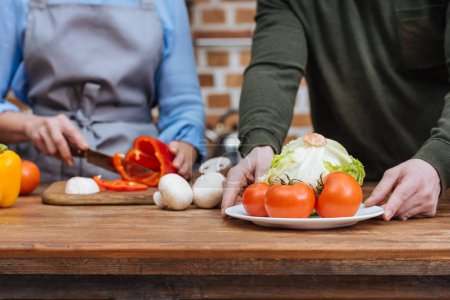 cropped image of couple preparing vegetables