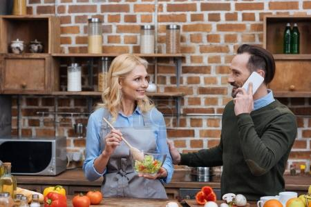 smiling wife mixing salad in kitchen and husband talking by smartphone