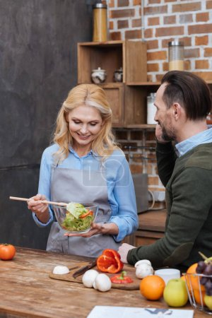 smiling wife mixing salad in kitchen