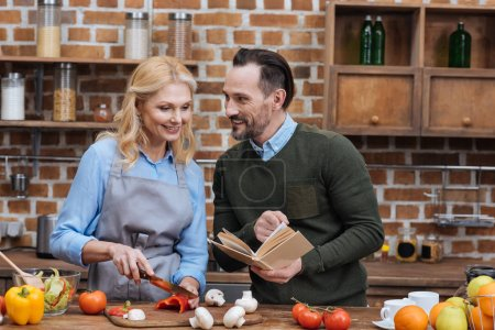 Photo for Husband showing something to wife in recipe book - Royalty Free Image