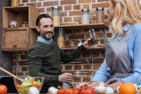 Photo for Smiling husband proposing wife spices in kitchen - Royalty Free Image