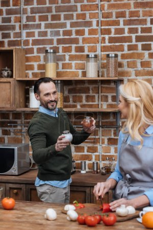 husband proposing wife spices in kitchen