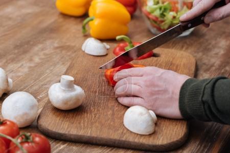 Photo pour Image recadrée de l'homme coupant poivron dans la cuisine - image libre de droit