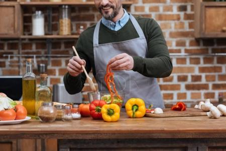 Photo for Cropped image of smiling man adding bell pepper to salad - Royalty Free Image