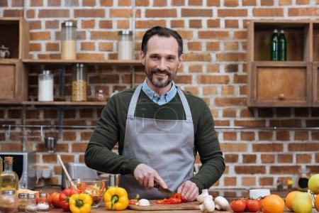 Photo pour Légumes coupe bel homme dans la cuisine - image libre de droit