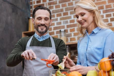 Photo for Happy affectionate couple preparing salad in kitchen - Royalty Free Image