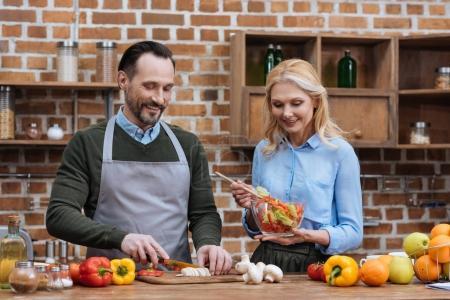 happy affectionate couple preparing salad