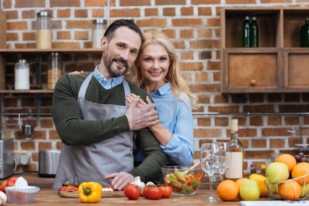 Photo for Happy husband and wife holding hands and looking at camera - Royalty Free Image