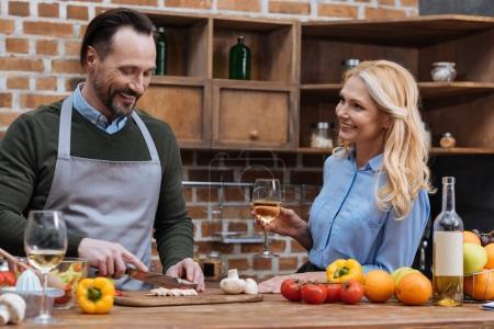 Photo pour Souriant, mari coupe légumes et femme debout avec verre de vin - image libre de droit