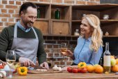 smiling husband cutting vegetables and wife standing with glass of wine