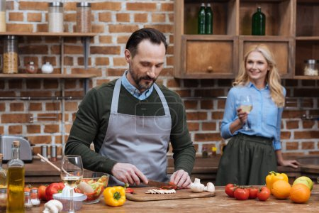Photo for Husband cutting vegetables and wife standing with glass of wine - Royalty Free Image