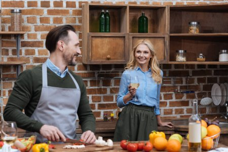 husband cutting vegetables and wife standing with glass of wine