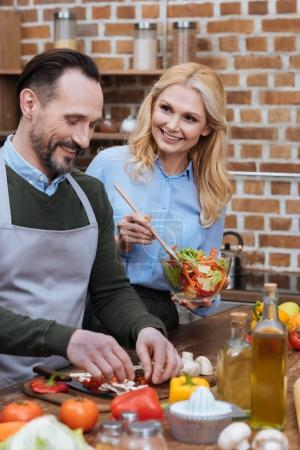 Photo for Happy husband and wife cooking together in kitchen - Royalty Free Image