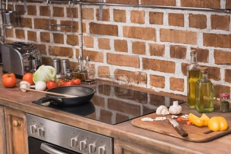 frying pan and wooden spatula on stove in kitchen