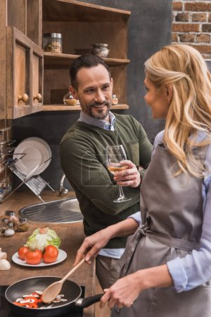 husband standing with wine near wife while she cooking at kitchen