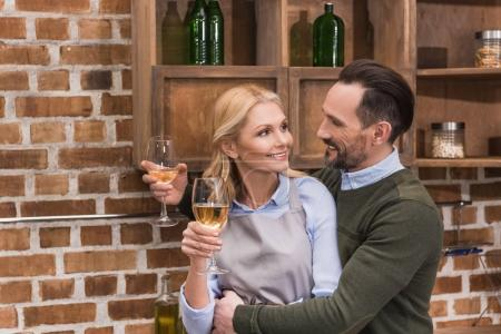 husband and wife with glasses of wine in kitchen