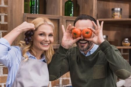 Photo for Wife and husband having fun and grimacing with pieces of vegetable and fruit - Royalty Free Image