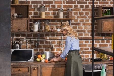 Photo for Side view of woman preparing at kitchen - Royalty Free Image