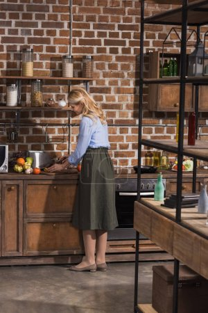 Photo for Side view of woman cooking at kitchen - Royalty Free Image