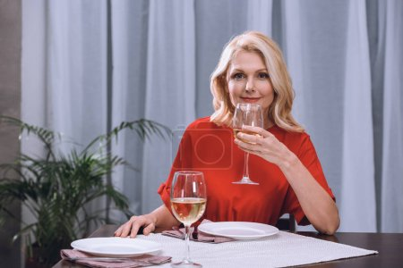 Photo for Attractive woman in red dress drinking wine at table - Royalty Free Image